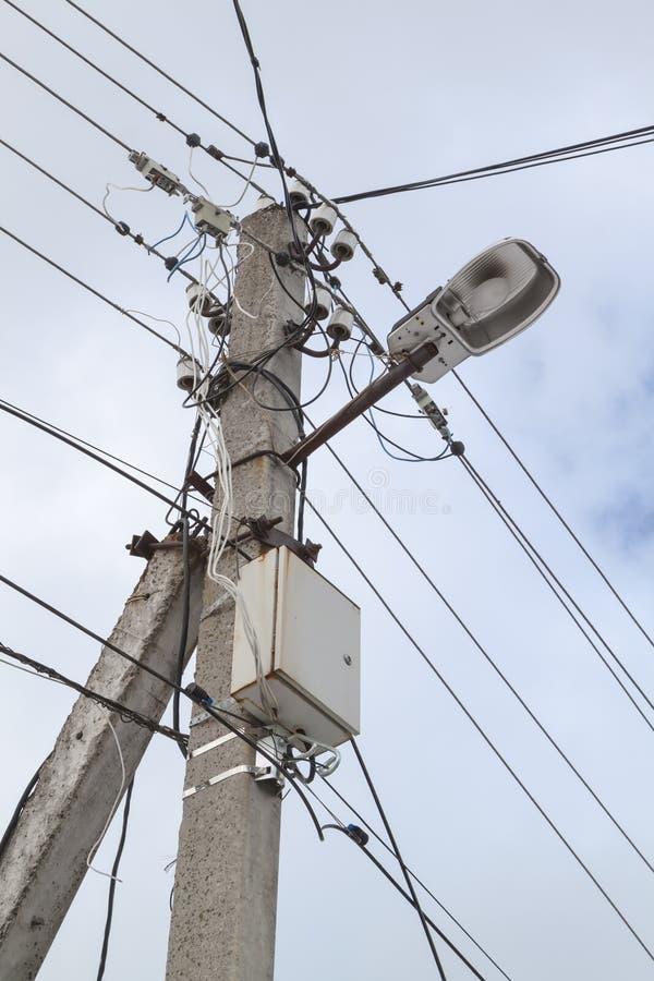 luz de calle en un poste de hormigón con gran número de alambres y medidor eléctrico automático foto de archivo