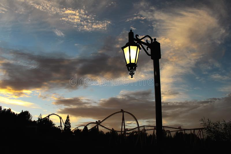 Luz de calle y una silueta de la montaña rusa en el fondo imagen de archivo libre de regalías