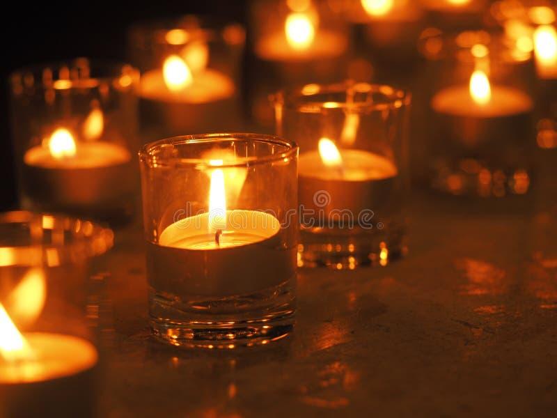 Luz de cristal de la vela con la profundidad del campo baja Burning ligero de las velas de oro de la Navidad de la llama de vela  imagen de archivo