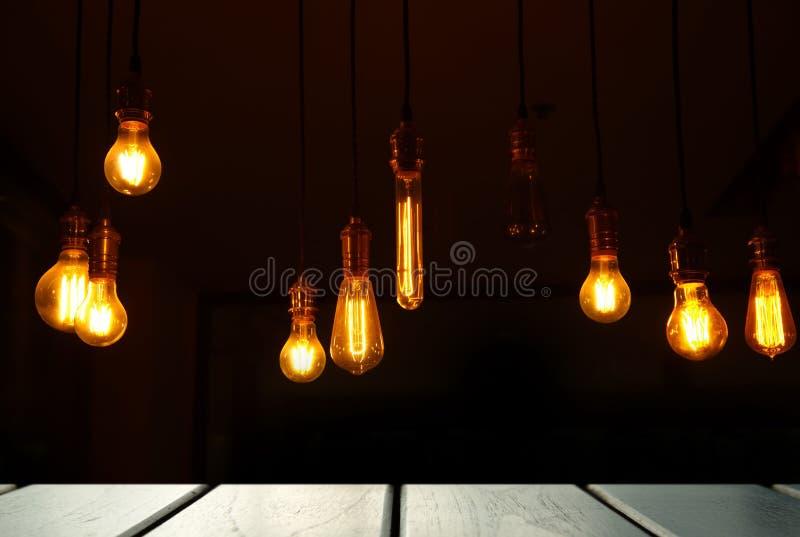 Luz de la lámpara con el fondo de exhibición de madera de la tabla del top del negro en la oscuridad fotografía de archivo