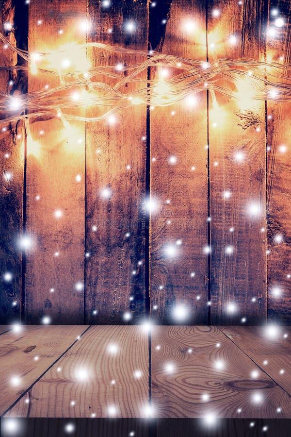 Luz de la Navidad, nieve en fondo de madera y tabla de madera con fotos de archivo libres de regalías