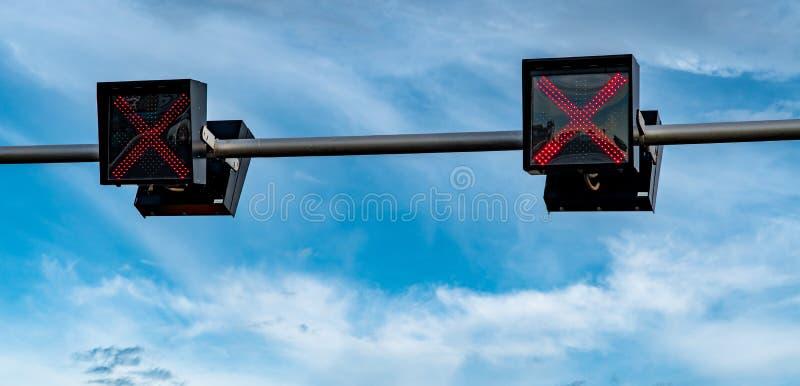 Luz de la señal de tráfico con color rojo de la muestra cruzada en el cielo azul y el fondo blanco de las nubes Muestra incorrect imagen de archivo libre de regalías