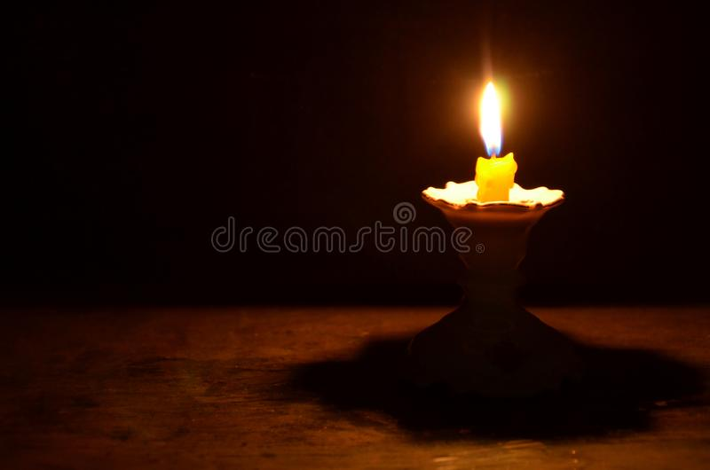Luz de la vela amarilla en el pedestal en la noche foto de archivo