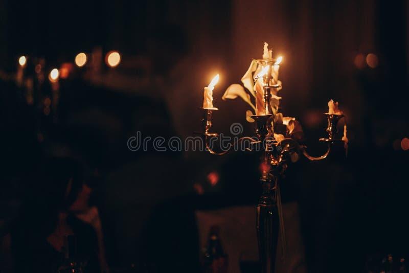 Luz de la vela velas que queman en la palmatoria de oro en iglesia en imagenes de archivo