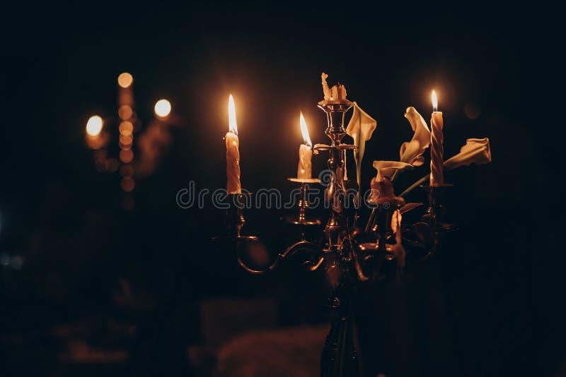 Luz de la vela velas que queman en la palmatoria de oro en iglesia en fotografía de archivo libre de regalías