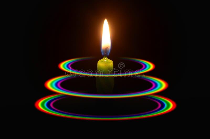 Luz de la vela verde en los tres anillos del arco iris fotos de archivo