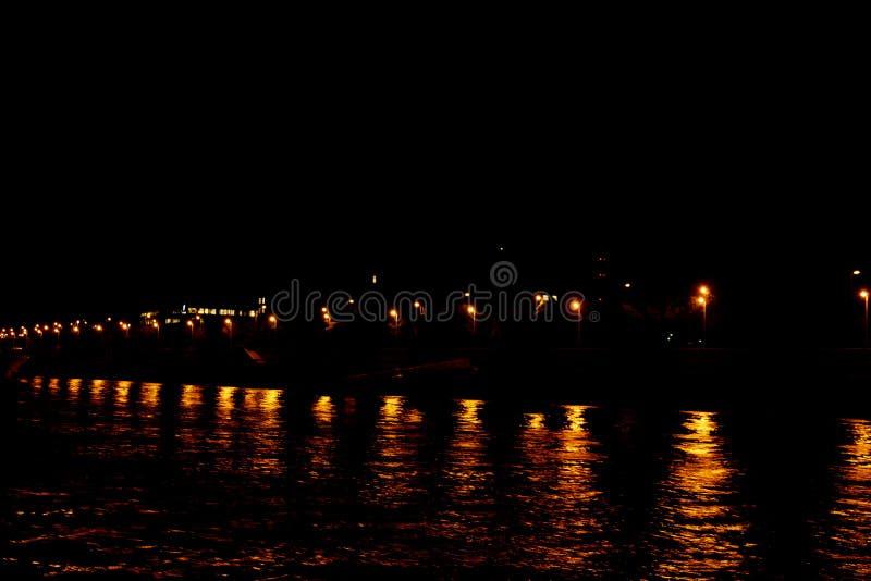 A luz de lanternas da cidade ? refletida na ?gua na noite Ondas no rio imagens de stock