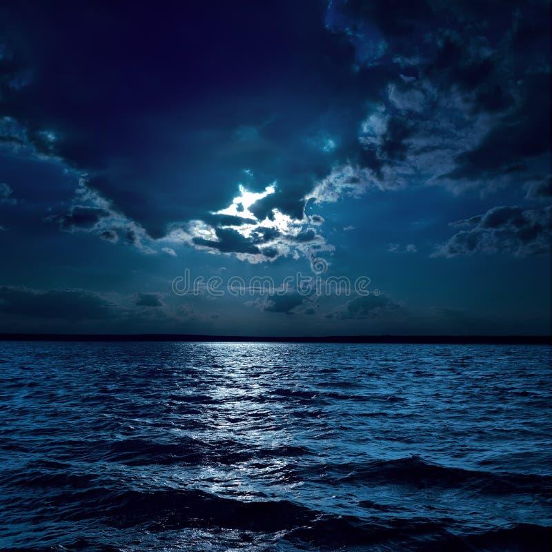 A luz de lua sobre escurece a água imagem de stock royalty free