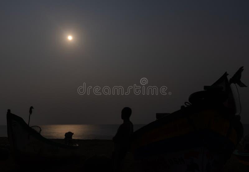 Luz de luna en la playa con el pescador y su sombra del barco foto de archivo