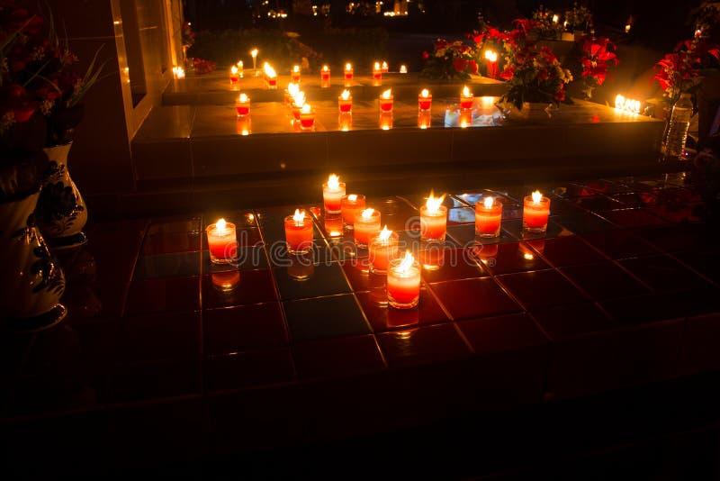Luz de muitas velas que incandescem na noite imagens de stock
