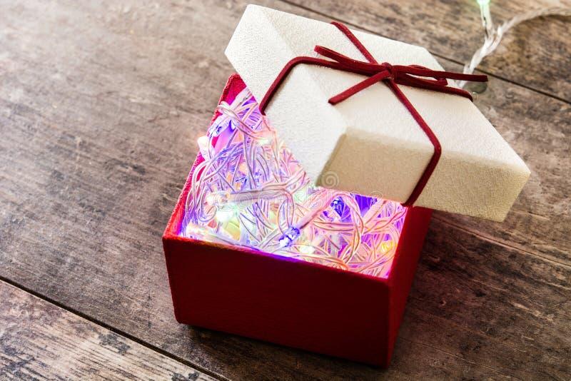 Luz de Natal dentro à caixa de presente vermelha na madeira fotografia de stock