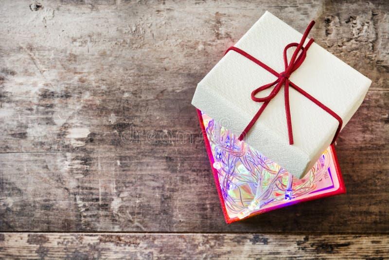 Luz de Natal dentro à caixa de presente vermelha na madeira fotos de stock