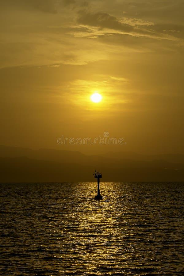 Luz de oro de la salida del sol detrás de las montañas y la sombra de la lámpara de señal para navegar en el mar imagenes de archivo