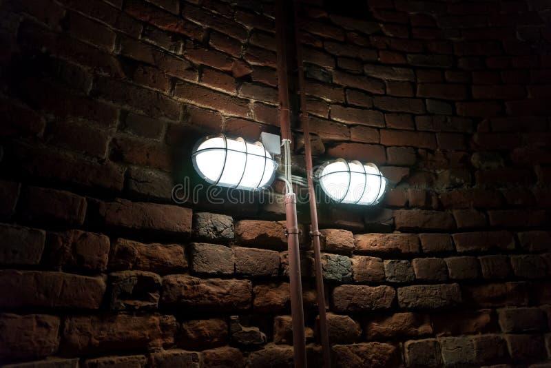 Luz de queimadura na parede de pedra do tijolo velho imagem de stock
