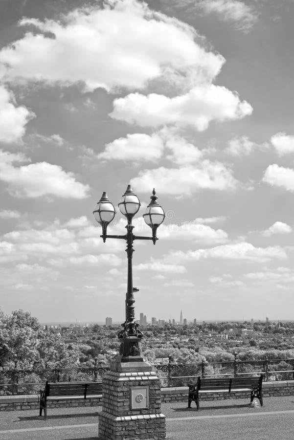 Luz de rua antiga com opinião da cidade de Londres imagem de stock