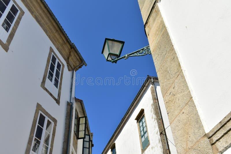 Luz de rua velha do ferro Paredes de pedra brancas com janelas de madeira Santiago de Compostela, Spain Dia ensolarado, céu azul fotografia de stock royalty free