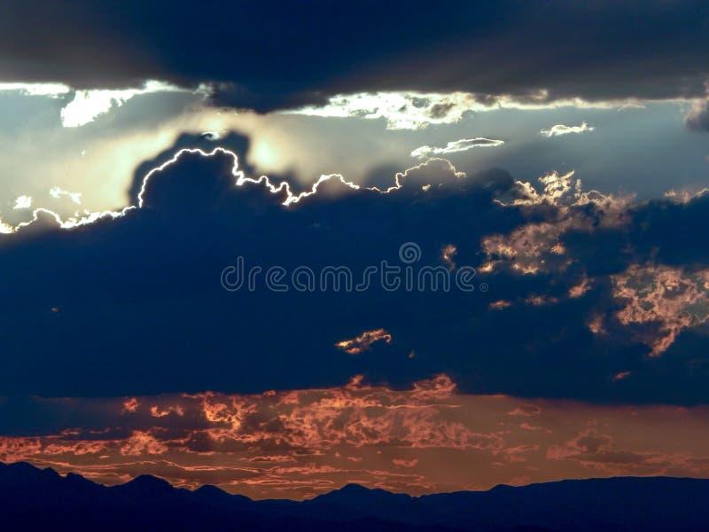 Luz de Sun que espreita atrás das nuvens escuras fotografia de stock royalty free