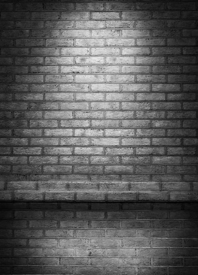 Luz de un reflector en una pared de ladrillo en un viejo cuarto Fondo de la pared de ladrillo con el punto ligero imágenes de archivo libres de regalías