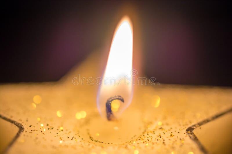 Luz de una vela de la Navidad de una vela asteroide delante de un fondo oscuro imagenes de archivo
