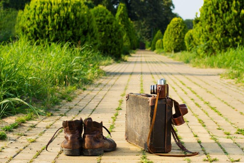 Luz de viagem! Botas, mala de viagem do vintage, câmera do filme, estrada amarela do tijolo foto de stock