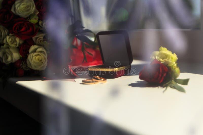 Luz del d?a en la ventana son los anillos de bodas hay las flores que son rosas rojas y blancas imagen de archivo