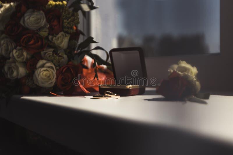 Luz del d?a en la ventana son los anillos de bodas hay las flores que son rosas rojas y blancas foto de archivo