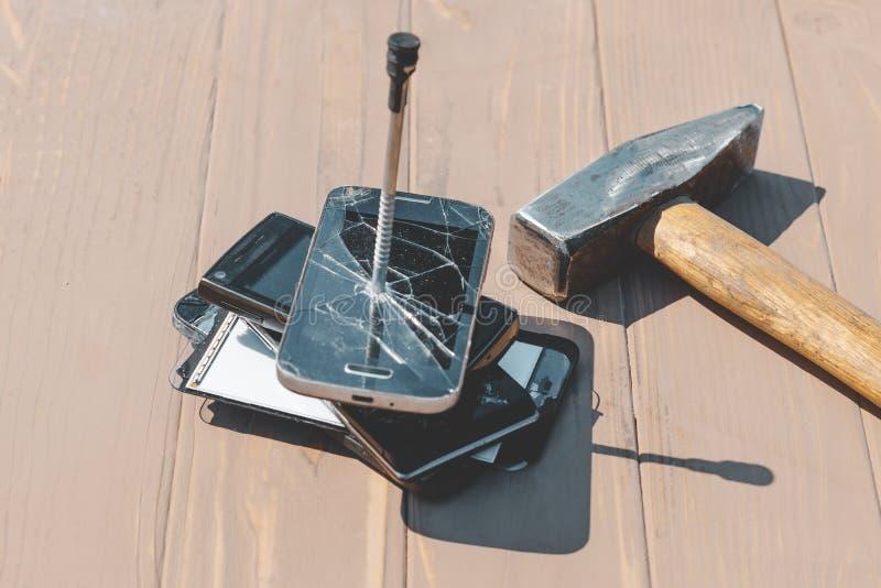 Luz del d?a martillo golpeado en los teléfonos en uno de ellos hay un clavo del metal foto de archivo