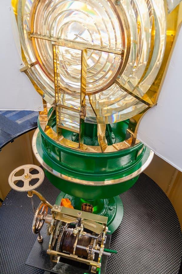 Luz del faro del Lit, con vistas al sistema óptico de Fresnel y al viejo mecanismo del reloj en la parte inferior foto de archivo libre de regalías