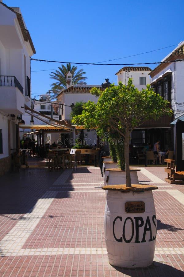 LUZ DEL LA DE ZAHARA DE LOS ATUNES COSTA DE, ESPAÑA - JUNIO, 19 2016: Área peatonal en centro de ciudad con las barras y los rest foto de archivo