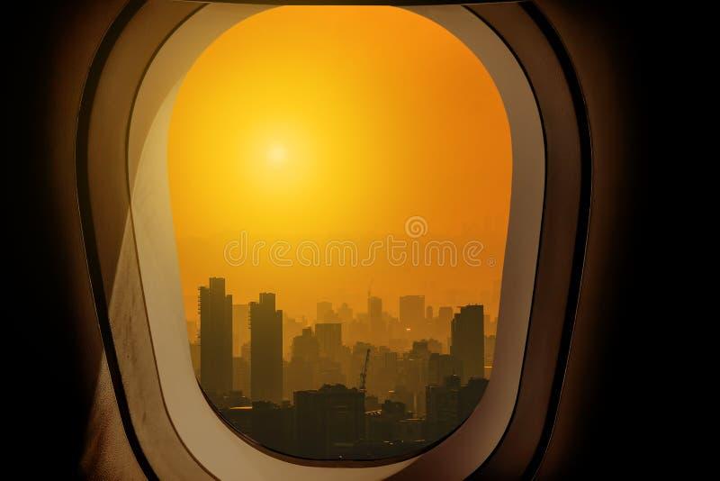 Luz del sol hermosa y paisaje urbano de la visión aérea a través de la ventana del aeroplano mientras que se acerca al aeropuerto imagen de archivo libre de regalías