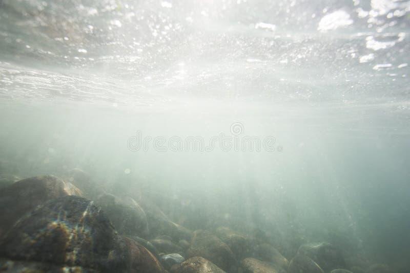 Luz del sol que brilla a trav?s de la superficie del oc?ano y que alcanza la cama de mar, incluyendo la arena y las rocas blancas fotos de archivo