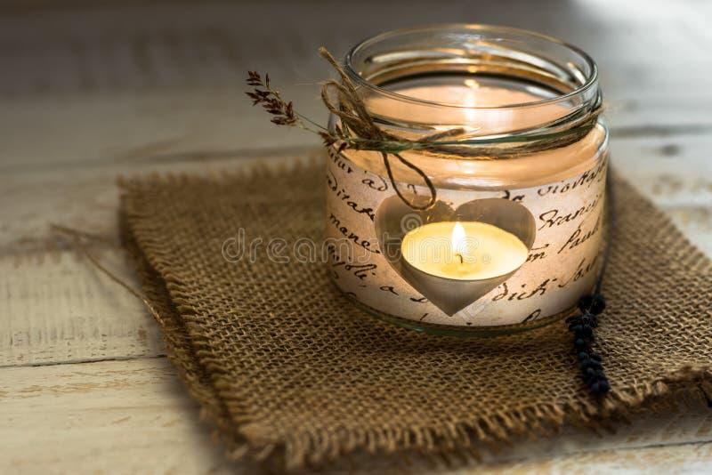Luz del té en candelero en forma de corazón del tarro con la ramita de la guita y de la lavanda, tarjeta del día de San Valentín, fotografía de archivo libre de regalías