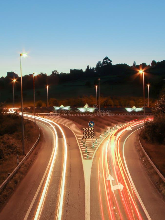 A luz do carro arrasta nos barcos da estrada e do papel em um carrossel fotografia de stock royalty free