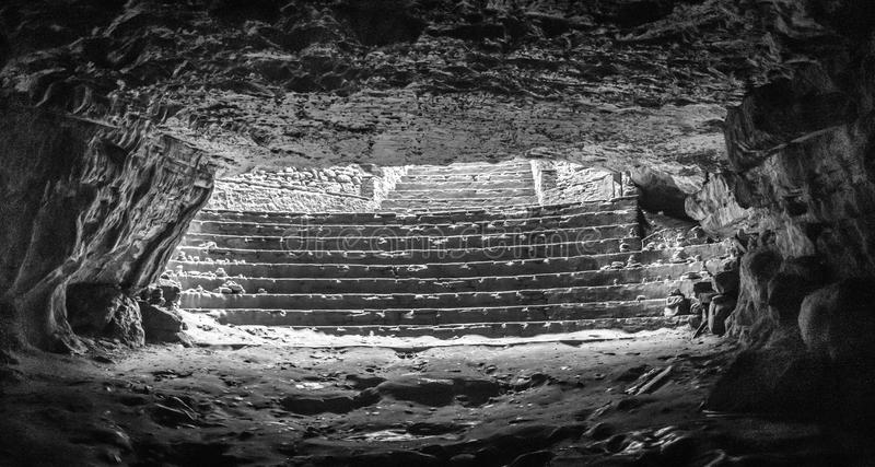A luz do dia pisca brilhantemente na escuridão da caverna do furo na parte superior dos cofres-forte da caverna, com a diferença  fotos de stock royalty free