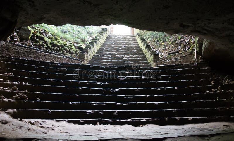 A luz do dia pisca brilhantemente na escuridão da caverna do furo na parte superior dos cofres-forte da caverna, com a diferença  imagens de stock royalty free