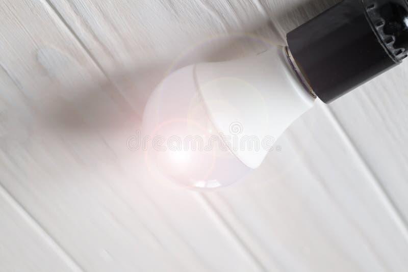 Luz do diodo emissor de luz em uma base escura Mentiras em um fundo de madeira Cor branca imagem de stock