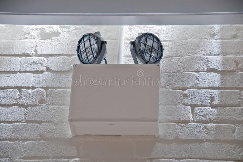 Luz do escurecimento da emergência instalada na parede de tijolo branca fotos de stock royalty free