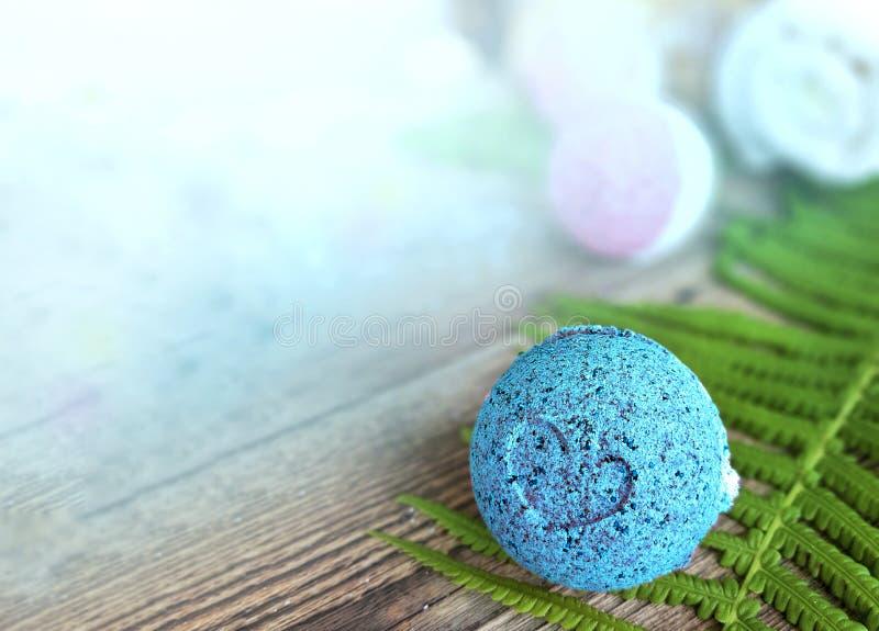 Luz do mar - bola azul do banho com a folha da samambaia no fundo de madeira foto de stock