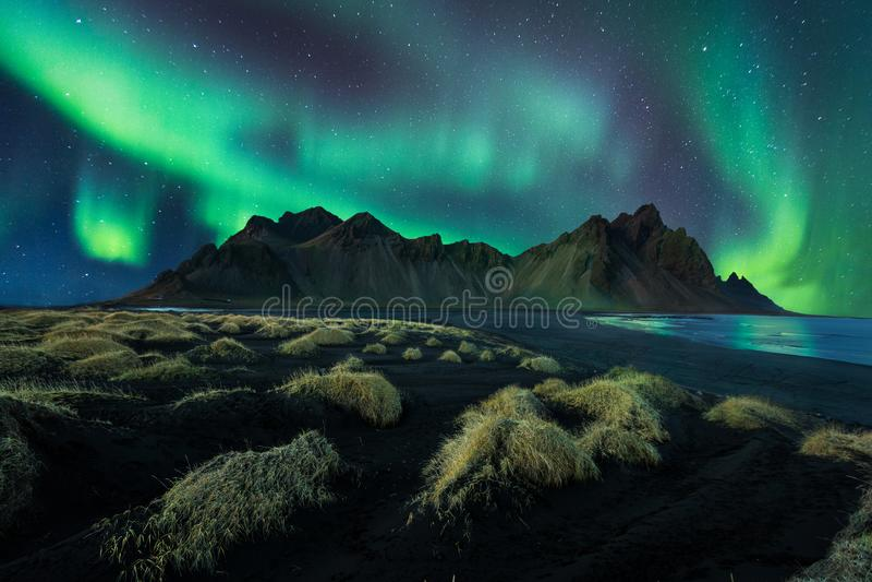 Luz do norte surpreendente da paisagem da noite de Islândia na montanha do vestrahorn com as dunas de areia pretas em stokksnes e imagem de stock royalty free
