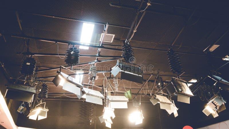 Luz do ponto que incandesce no fundo do teto do estúdio A lâmpada iluminada na fase do entretenimento desvanece sobre o tom foto de stock