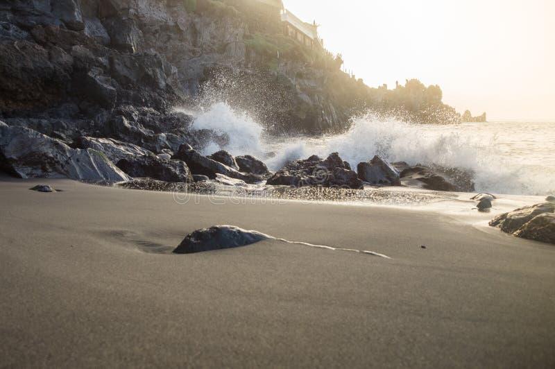 Luz do por do sol sobre a onda que espirra na praia vulcânica rochosa fotos de stock