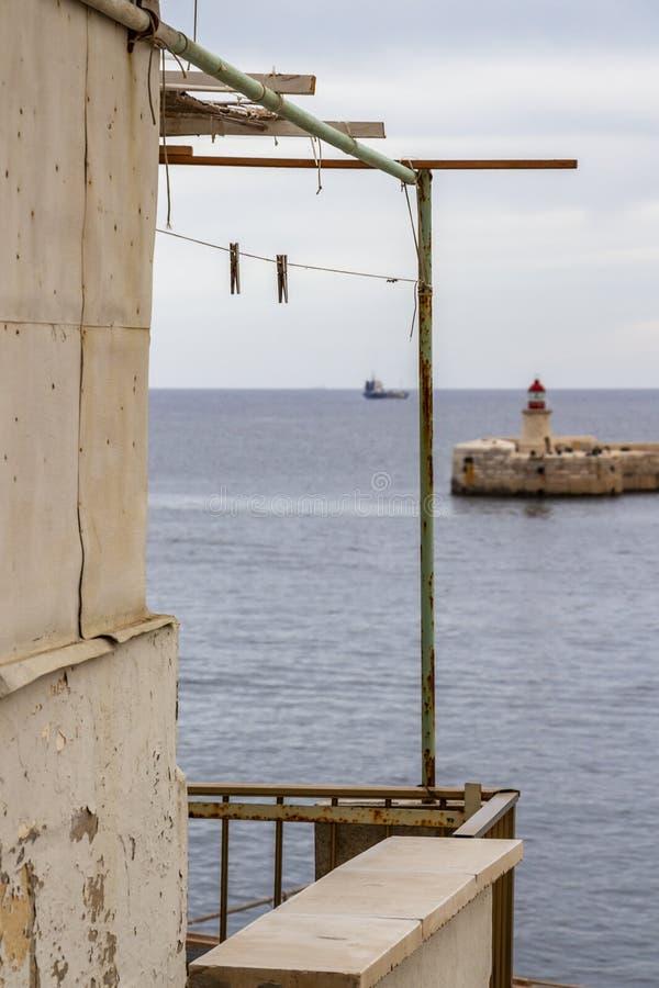 Luz do quebra-mar de Ricasoli e um navio no porto grande, Malta fotos de stock royalty free