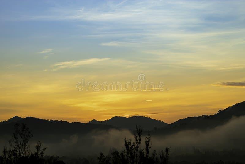 A luz do sol da manhã atrás das montanhas e da névoa foto de stock royalty free