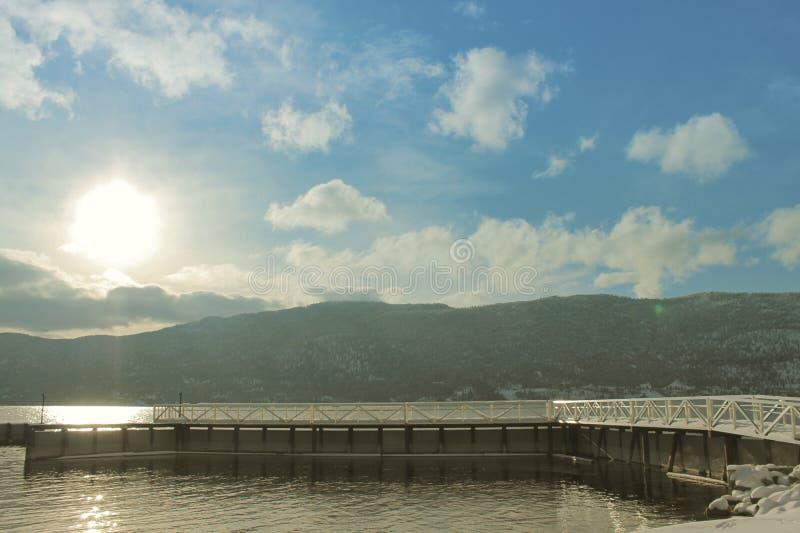 Luz do sol e raios no lago com a doca no inverno fotografia de stock royalty free