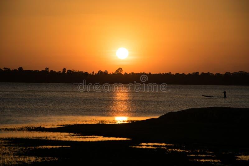 A luz do sol na noite, tem o esporte de barco do pescador dentro do rio, sol fotografia de stock