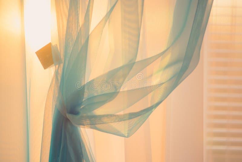 Luz do sol do por do sol através das cortinas finas na janela foto de stock royalty free