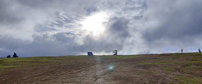 Luz do sol que quebra através das nuvens chuvosas da monção em uma cume foto de stock royalty free