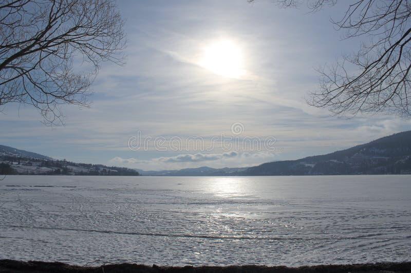 Luz do sol que reflete no lago congelado com montanhas e horizonte fotografia de stock