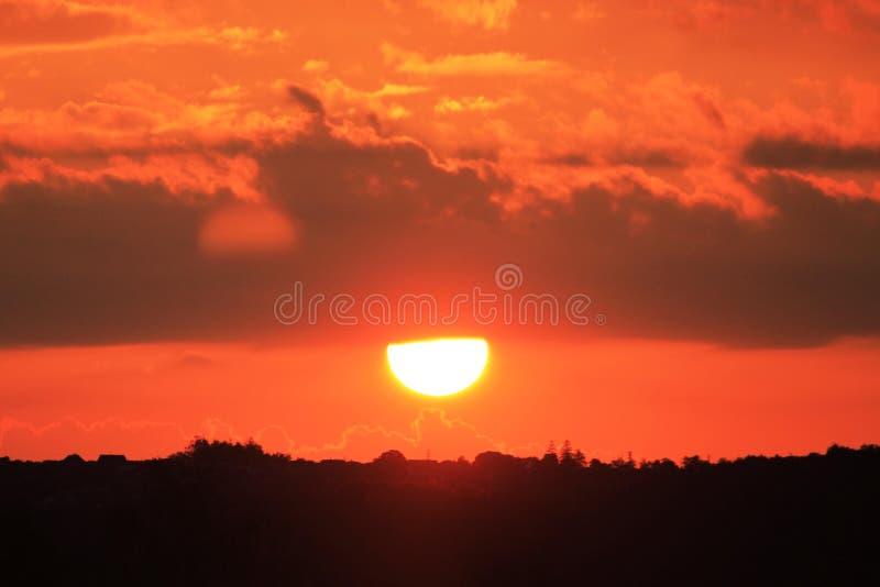 Luz do sol vermelha com nuvens cinzentas imagem de stock
