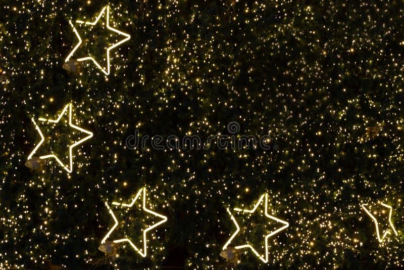 Luz dourada da decoração na forma da estrela no pinheiro do Natal imagens de stock